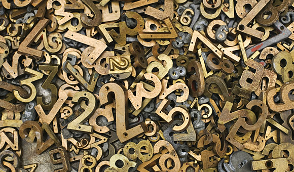 brass three dimensional numbers in a large pile photo