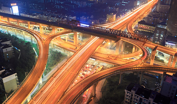 night scene of busy highway system seen from above with over and under passes phtos