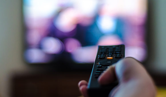 closeup of hand holding tv controls with blurry tv in background photo
