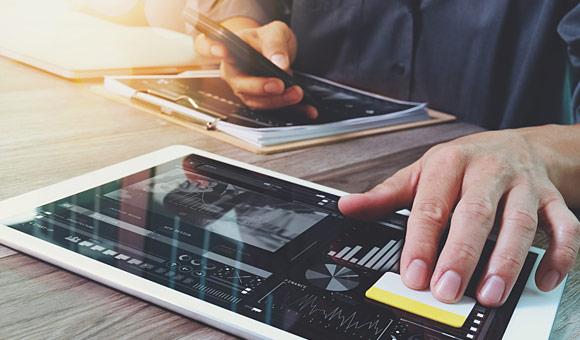 一只手拿着手机触摸平板电脑屏幕照片的特写镜头。