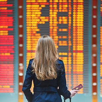 woman traveler holding passport looking at airport arrival and departure board photo