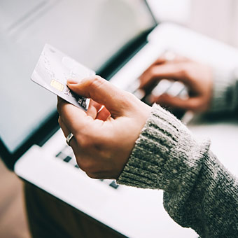 woman holding credit card as she enters numbers into computer laptop photo