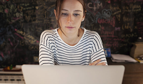 young woman looking at laptop in concentration