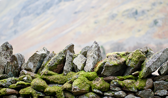 wall of old jagged rocks with moss blurred mountain side in background photo