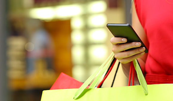 woman with shopping bags and smart phone photo