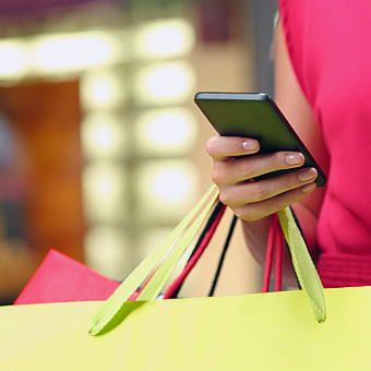 woman with shopping bags and smart phone
