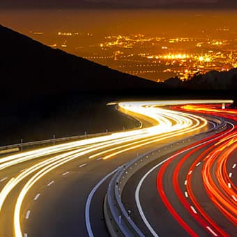 long exposure photo of cars on a winding highway at night