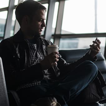 man sitting in airport on phone