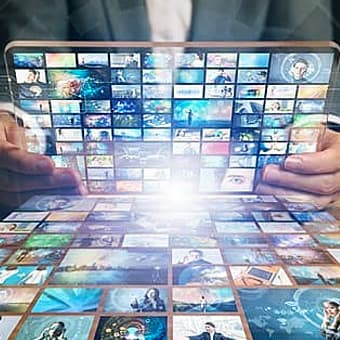 abstract image of man holding laptop with multiple television screens