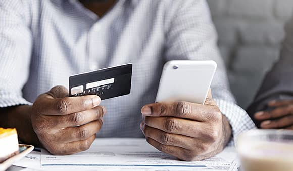 man making purchase with credit card on phone